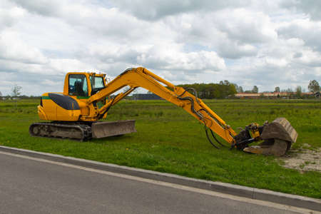 yellow mini excavator with a beautiful blue cloudy sky Imagens