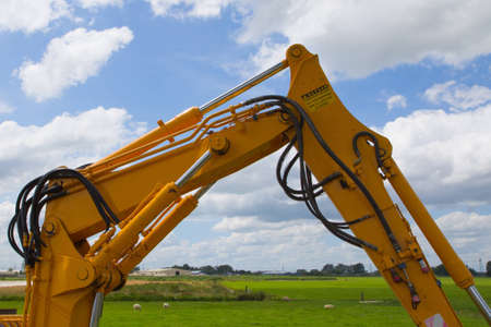 the articulation of a yellow mini excavator with a cloudy sky as background Imagens