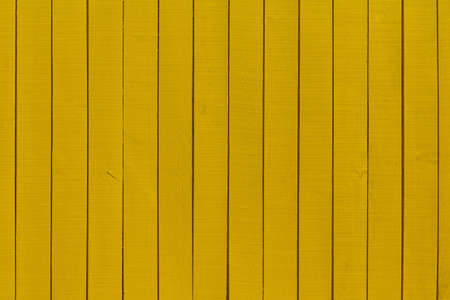 screwed: a yellow fence where the boards are screwed