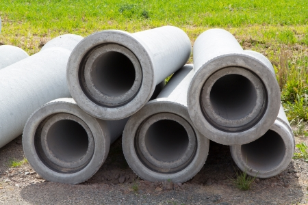 five sewer pipes made of concrete lying in the sand Stock Photo - 17991180
