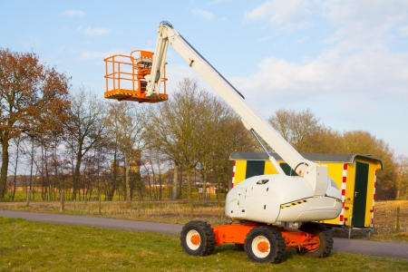 an aerial platform for pruning trees with the sky as background photo