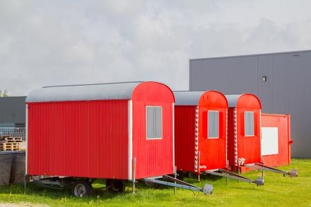 tres casetas de obra de color rojo en las ruedas y un contenedor Foto de archivo - 20001987