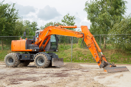 hydraulic hoses: orange excavator for leveling a sand bed
