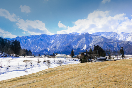 close range: Hakuba mountain range  and  Hakuba village houses  in the winter with snow on the mountain and blue sky and clouds background in Hakuba  Nagano Japan.