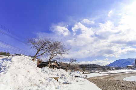 Hakuba mountain range  and Lake in the winter with snow on the mountain and blue sky and clouds background in Hakuba  Nagano Japan. Stock Photo