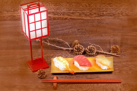 Japanese food ,sushi with chopsticks on wooden table wall background . Stock Photo