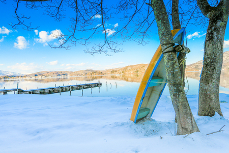 Beautiful fresh snow in winter around the mountains  Lake ,and tree  ,boat with blue sky  background, Nagano Prefecture, Japan. Stock Photo