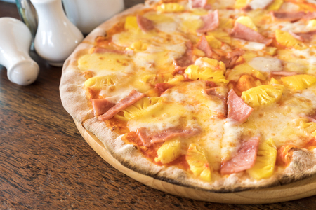 ham and pineapple pizza on wooden table Banco de Imagens
