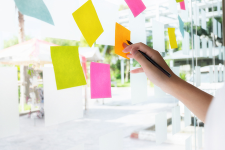 business people post it notes in glass wall at meeting room