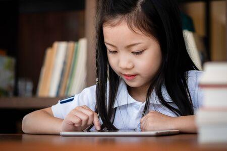 Linda chica sonríe sentada y jugando computadora portátil en la biblioteca, concepto de niños, concepto de educación Foto de archivo