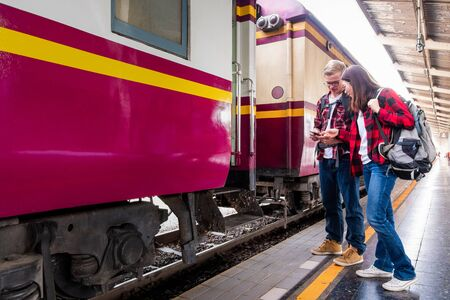 Happy young couple travellers together on vacation at the train station, travel concept, couple concept