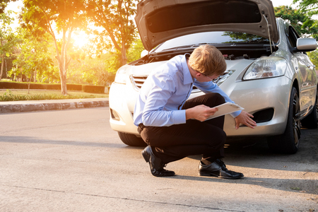 Insurance agent writing document on clipboard examining car after accident, Insurance concept Reklamní fotografie