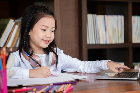 cute girl smiled and sitdown to drawing a book in the library, children concept, education concept