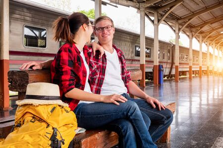 Happy young couple travellers together on vacation at the train station, travel concept, couple concept Banco de Imagens