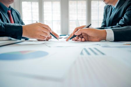 Gli uomini d'affari che analizzano il grafico degli investimenti incontrano il brainstorming e discutono il piano nella sala riunioni, il concetto di investimento