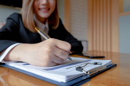 young woman sitting for candidate at job interview and writing resume on application form in office, job interview, interview concept Stock Photo