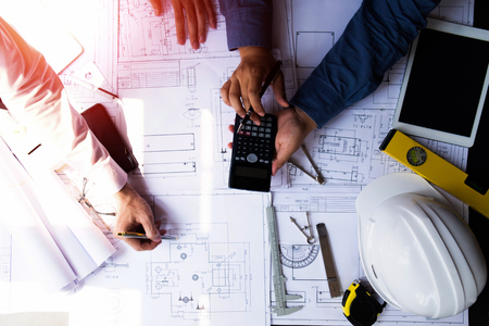 engineers pointing to building on blueprint and using laptop to drawing design building Project in office, construction concept. Engineer concept Banco de Imagens - 124368880