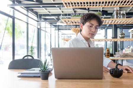 Joven empresario que trabaja con un portátil móvil y documentos en la oficina, concepto de negocio Foto de archivo