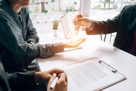 Agents immobiliers détenant une maison modèle et des clés pour soumettre des documents aux clients à signer pour un contrat de vente, concept immobilier.