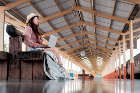 Smiling woman traveler with backpack using laptop to planning vacation on holiday relaxation at the train station, relaxation concept, travel concept Banco de Imagens