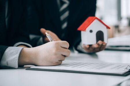 Immobilienmakler reichen Dokumente ein, damit Kunden einen Kaufvertrag unterzeichnen können Standard-Bild