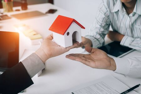 Real estate agents holding model house and give for customers with sale contract,real estate concept.