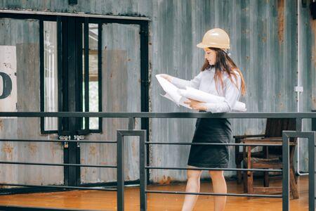 young engineers wearing helmat looking blueprint modern project in the office, Engineer concept Banco de Imagens