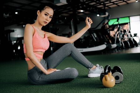 sport woman at fitness gym club sitting relaxing after exercise with kettlebell and dumbbells, fitness concept, sport concept