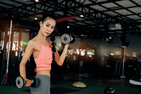 sport woman at fitness gym club doing exercise for arms with dumbbells and showing muscle bodybuilding, fitness concept, sport concept