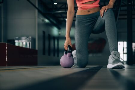 sport woman at fitness gym club doing exercise for arms with kettlebell and showing muscle bodybuilding, fitness concept, sport concept Banco de Imagens