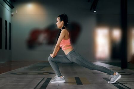 sport woman at fitness gym club warm-up and stretch body before doing exercise, fitness concept, sport concept