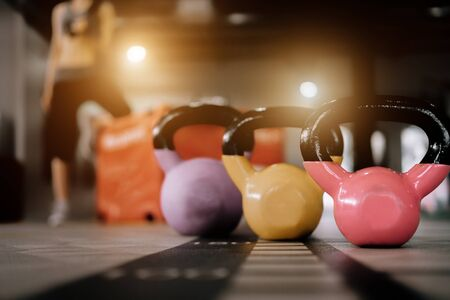 kettlebell in front of sport woman at fitness gym club doing exercise for arms with dumbbells, fitness concept, sport concept