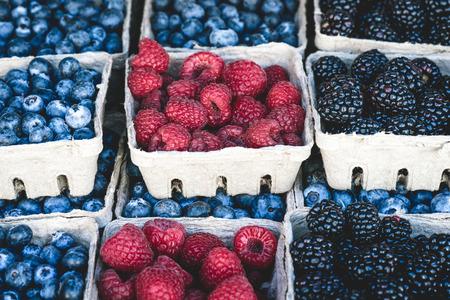 Raspberries, blackberries and blueberries background in small baskets for sale at market. 版權商用圖片