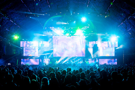 lighting effects musician: Live  concert music festival and party people enjoying the live performance of different artist with the dazzling, sparkling and colorful digital disco lights Stock Photo