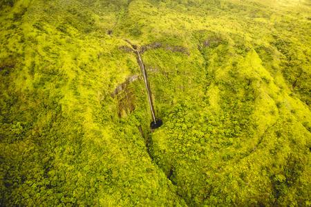 Breath taking dramatic waterfall in Maui, Hawaii national park. Dramatic landscape yellow green tropical rain-forest of Maui, Hawaii. Waimoku falls aerial view.
