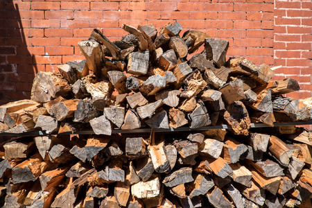 Stacked pile of wood with real brick in the background. On the streets of New York.