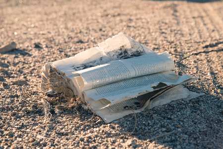 Old washed up, damaged, rough and  dirty book in desert