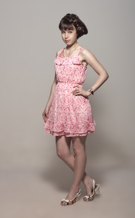 bright eyed: Beautiful girl posing in a pink dress and sandals Stock Photo
