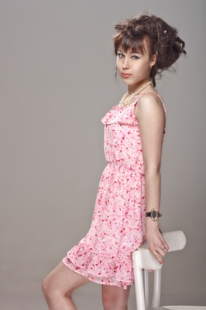 relies: Beautiful girl posing in a pink dress relies on a chair