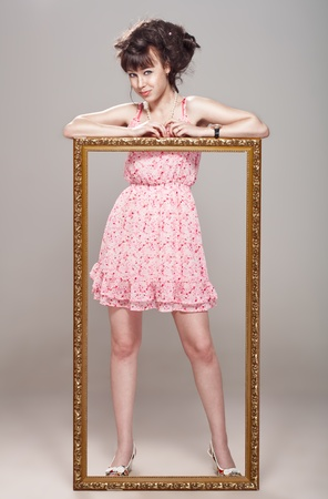 wide eyed: Beautiful girl posing in a pink dress, stilettos and pattern frame