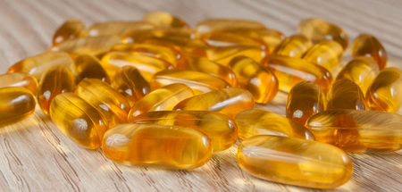 Omega3 fish oil capsules in fish shape on wooden background Stock Photo