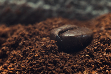 Grain of fragrant coffee macro closeup lying on a pile of ground