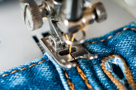 sewing process denim material. closeup dirty claw old sewing machine Stock Photo