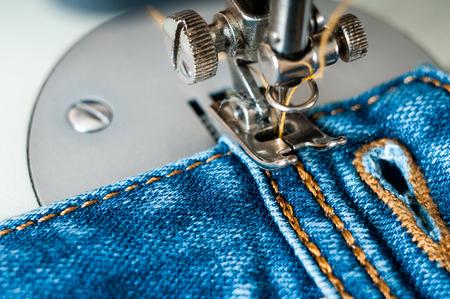 sewing process denim material. closeup dirty claw old sewing machine Standard-Bild