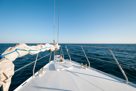 A wide angle shot of the front of the yacht in the summer sailing towards the horizon Banco de Imagens