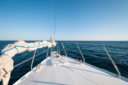 Eine Weitwinkelaufnahme von der Vorderseite der Yacht im Sommer, die in Richtung Horizont segelt Standard-Bild