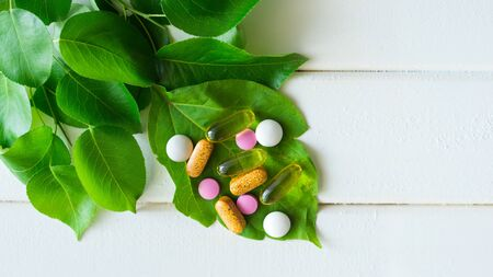 capsules omega fishing oil, pills and vitamin on green leaf closeup on white wood background