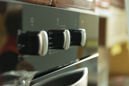 punch press: The control panel of kitchen oven black