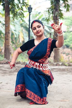 portrait of beautiful young Indian classical odissi dancer wears traditional costume and posing Odissi dance mudra in the rainforest. Stock Photo - 149604531