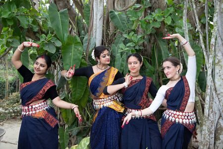 multinational group of beautiful young classical odissi dancers wears traditional costume and posing Odissi dance mudra in the rainforest.